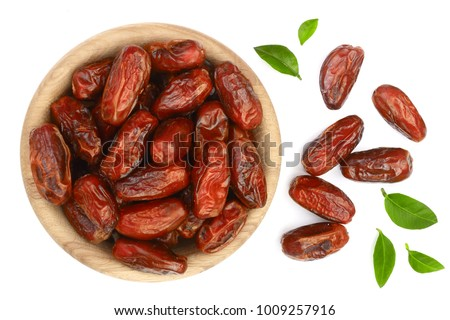 dry dates with green leaves in wooden bowl isolated on white background. Top view. Flat lay pattern #1009257916