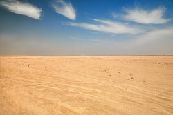 Dry desert landscape. Hot lifeless sand of desert and blue sky in summer sunny day. Flat desert of Egypt. Travel and tourism concept.