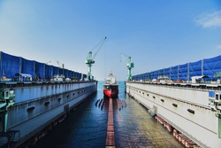 Dry dock with Cargo Ship maintenance or repair at floating dock in shipyard both deck crane loading during bring ship in to the dry dock.