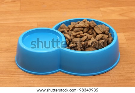 dry dog food and water in blue bowl on the floor