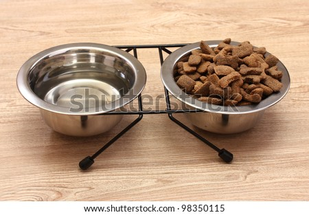dry dog food and water in metal bowls on wooden background - stock photo
