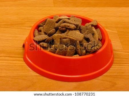 dry dog food in orange bowl on the floor