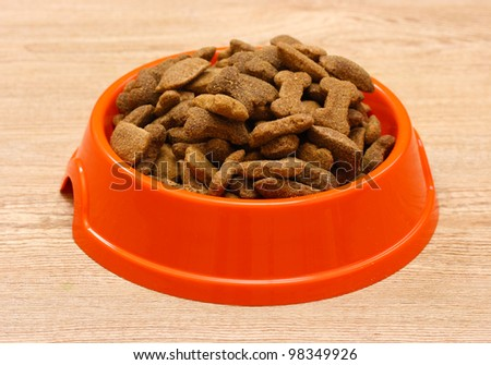 dry dog food in orange bowl on wooden background