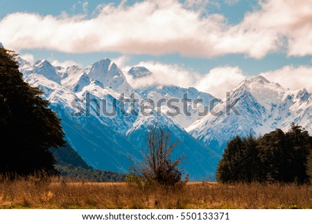 Dry flat plain in the foreground and snow mountains in the background #550133371