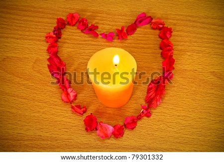Dry flower heart with candle on wood background