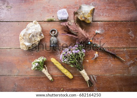 Dry flowers, a thistle, a staff of feathers, a crystal of quartzite and candles made from natural wax, witchcraft, spells, magic, Wicca, the goddess #682164250