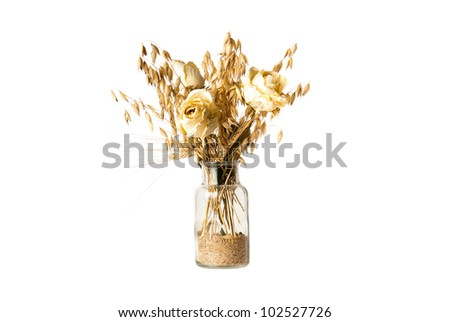 dry flowers and barley in bottle with sand - stock photo