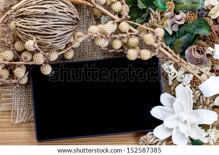 Dry flowers frame on wooden background with tablet computer (tablet pc)