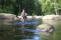 Dry fly fishing. Fly fishermen in a French trout river. Fishing scene focused on fly fishing lure