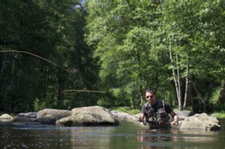 Dry fly fishing. Fly fishermen in a French trout river. Fly fishing casting scene