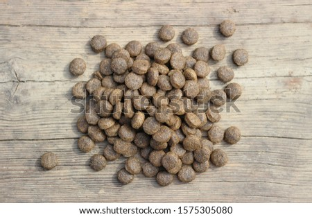 Dry food for any animals in granules on a wooden table.