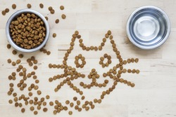 Dry food for cats. Two bowls. Wooden surface. Cat shape. Some cat crunchies are on wooden surface, out of the bowl and forms a pattern in the shape of a cat.