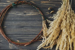 Dry grass and twigs in circle on rustic wooden dark background. Making stylish boho autumn wreath with wildflowers and herbs. Space for text. Holiday workshop