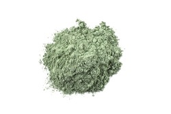 Dry green cosmetic clay isolated on white background. Heap of natural organic green cosmetic clay.