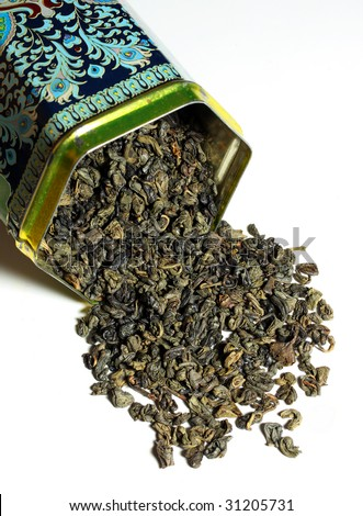 Dry green tea - The tea plant is commonly used in Chinese herbalism, where it is considered to be one of the 50 fundamental herbs.  Ornament in dose is noname folk art. - stock photo