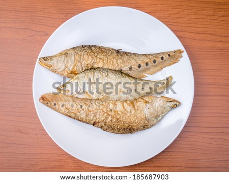 dry grilled smoked featherback fish ( preserve food ) on white dish on wood background
