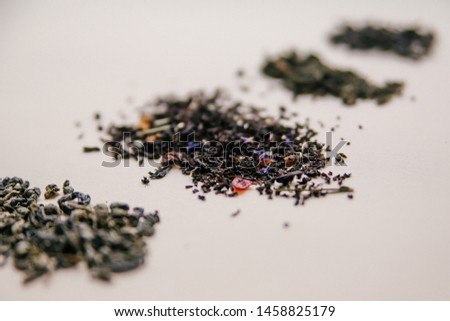 Dry herbs and different types of tea leaves in bunches on a calm background. Shallow depth of field. Focus on the medium bunch.
