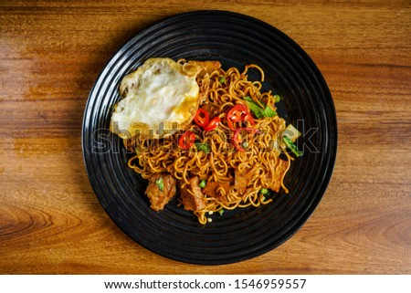 Dry Instant Noodle, Malaysian style maggi goreng mamak or spicy dry curry instant noodles with sunny side up egg and beef.