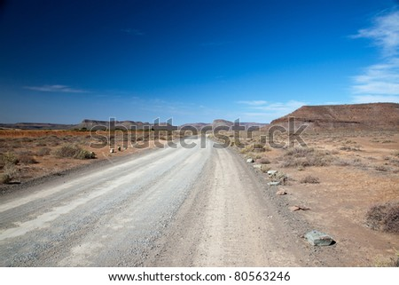 Dry landscape in South Africa with a lonely road or highway with a vision and a clear blue sky - horizontal