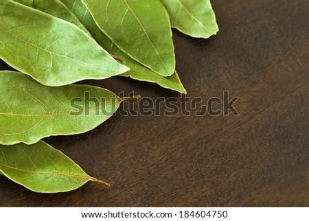 dry laurel leaves (Laurus nobilis) on wooden background