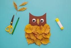 dry leaves applique art autumn. little child making autumn decoration
