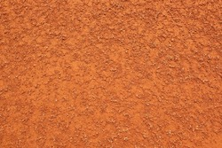 Dry light red crushed bricks surface on outdoor tennis ground. Detail of rough texture