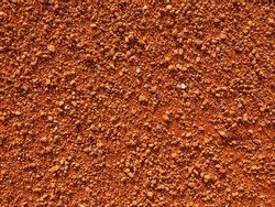 Dry light red crushed bricks surface on outdoor tennis ground. Detail of texture