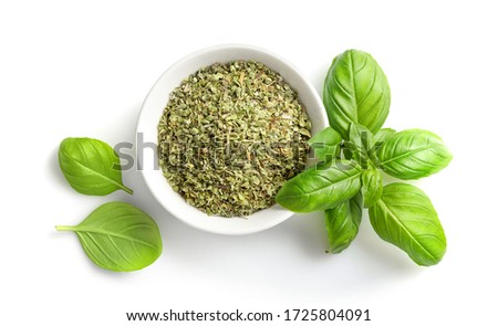 Dry marjoram in bowl and fresh basil leaves isolated on white background. Top view. Stock photo ©