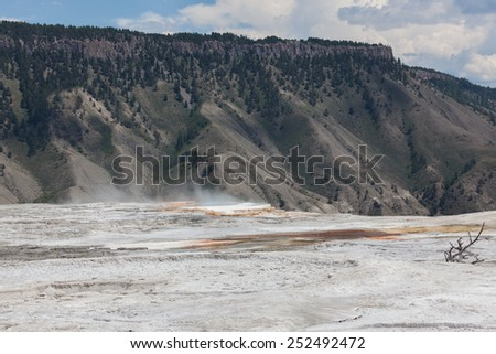 Dry mineral flats with an area of hot steam and water that drops off a ledge with distant mountains in Yellowstone National Park.