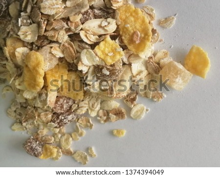 dry musli with oats, cornflakes, nuts and and raisin on a white background  #1374394049