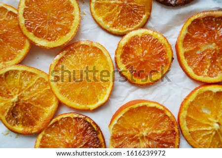 Dry oranges on baking paper background. Dried slices of orange in sugar syrup. Drying process.