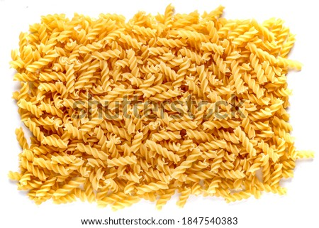 Dry pasta fusilli. Fusilli have spiral shape and yellow color. Pasta is delicious Italian traditional food made from wheat flour like noodles.Pasta background.Top view Foto d'archivio ©