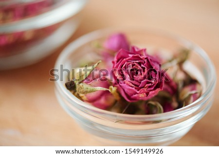 Dry pink rosebud in small glassware that can be used in process of soap making standing on table #1549149926