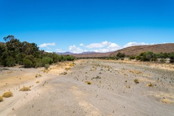 dry river bed in a valley with bridge at the bottom end in the town of Laingsburg, Karoo, South Africa where drought is apparent in a desert like environment concept water conservation and save earth