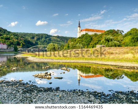 Dry riverbed of river Elbe in Decin, Czech Republic, summer 2018. Empty river bed with poisoned muddy water. Decin castle above old railway bridge.