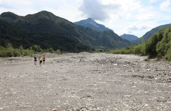 dry riverbed of the stream and a family walking among the stones in summer