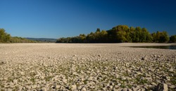 Dry riverbed on a nice autumn day with visible trees.