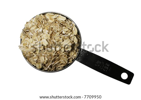 dry rolled oats or oatmeal in a metal half-cup scoop isolated on white