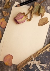 Dry rose and old book on a wooden background with space for information