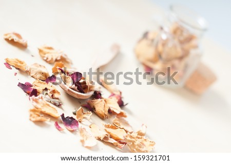 Dry rose petals with a wooden spoon and a small glass pot