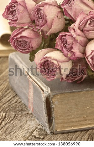 Dry roses on an old book in a vintage style