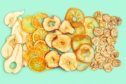 Dry slice fruits apple, banana, persimmon, tangerine, pear. Tasty dehydrated mix fruit chips. Trendy food for vegetarian. Bright colors flat lay.