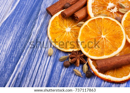 Dry slices of orange, cinnamon, allspice and cardamom on a blue wooden background #737117863