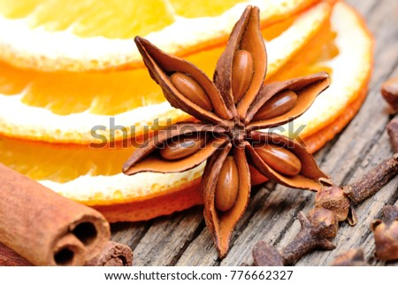 Dry slices of orange with anise star cinnamon and cloves on rustic table