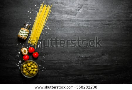 Dry spaghetti with olives, tomatoes and salt. On a black wooden background. Free space for text . Top view
