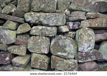 dry stone wall with green lichen