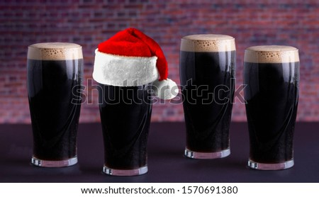 Dry stout beer dark pints with a Holiday santa hat. SantaCon concept. Stock photo ©