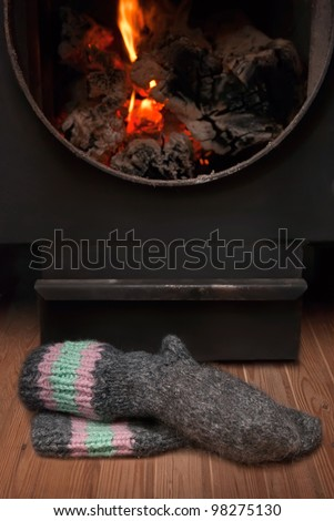 Dry the feet of white woolen socks by the fire stove