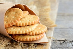 Dry thin crackers in a wrapping paper and on a sackcloth. Old wooden background. Tasty crispy crackers cookies idea for children and adults. Closeup