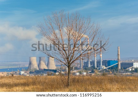 Dry tree against power plant with smoke pipes